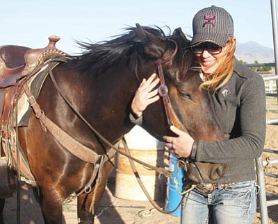 Sharla Wilson and River Dance, a wild mustang that Wilson trained in 100 days to win Extreme Mustang Makeover-Arizona, share a tender moment. Wilson received $7,000 in prize money and half of River Dance's adoption price of $3,000. A new owner, who lives in New York, is paying Wilson to keep the horse for a year and continue to train him. JC AMBERLYN/Miner