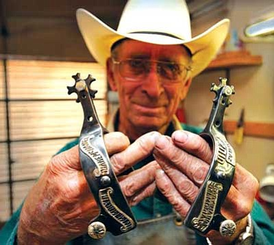 """<i>Todd Roth/NHO</i><br> Leon King, who has over 50 years of experience in making hand-made spurs, shows a pair of his """"famous"""" spurs. He got his start after purchasing an inferior pair of spurs from a mail-order catalog. Today, he produces about 25 pairs a year. Among the notables who own King spurs is former Navajo Nation President and State Sen. Albert Hale."""