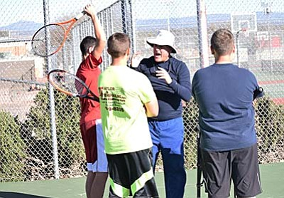 Larry Lineberry (middle) gives serving instruction to some of his players during a preseason practice earlier this year. (Photo by Greg Macafee)