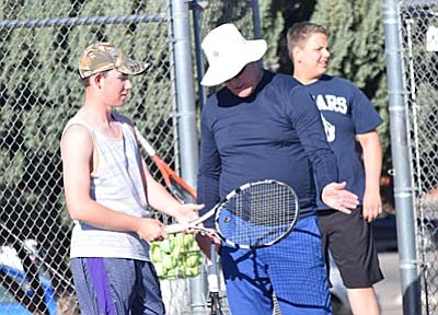 Larry Lineberry, right, teaches one of his Mingus Union tennis players about form during a practice at Mingus Union High School earlier this year. (Photo by Greg Macafee/VVN)