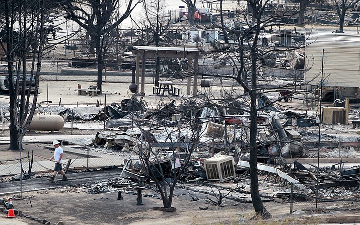 A worker walks past burned out mobile homes in South Lake, Calif., Tuesday, June 28, 2016, after a wildfire devastated the area.