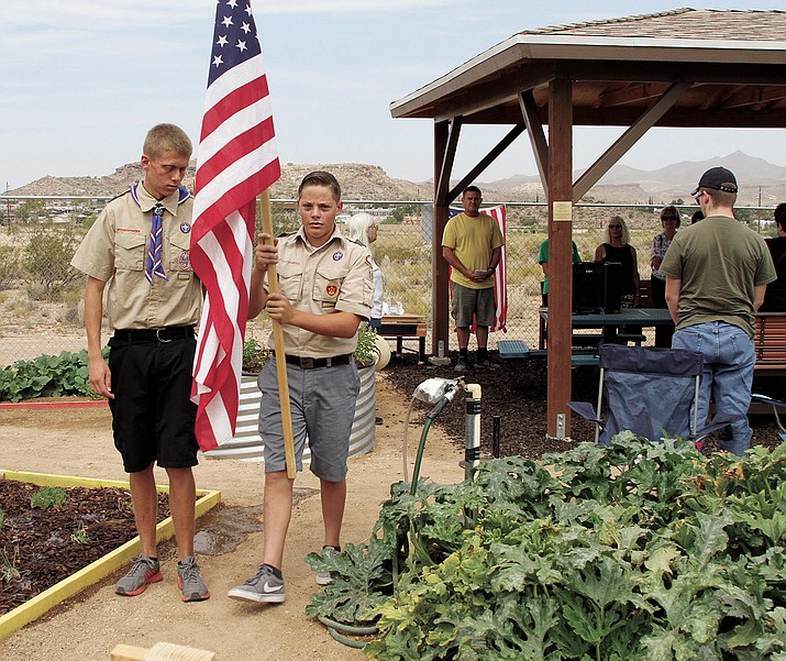 Eagle Scout Garrett Hoffman (holding the flag) and Brendon Allred perform a flag ceremony on Saturday next to the ramada they built.