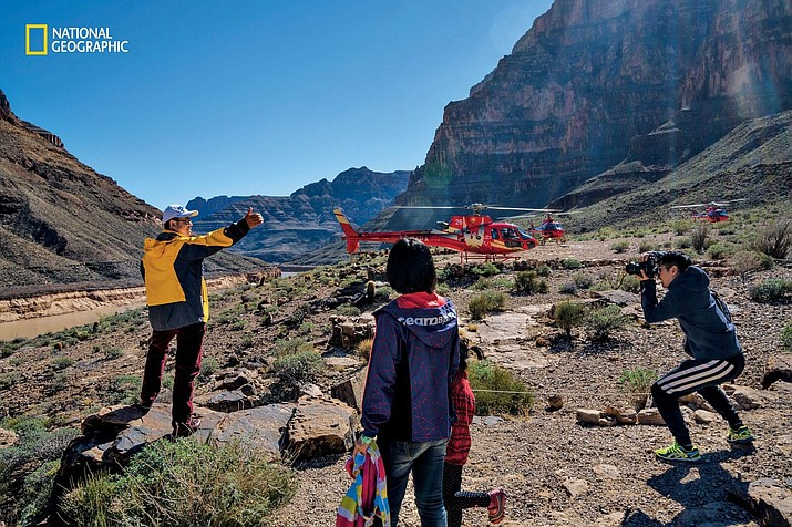 Tourists document a flight into Grand Canyon West in this image from the September issue of National Geographic magazine. In 2015, helicopter tours helped draw over a million visitors to Hualapai land. Last spring, in an area known as Helicopter Alley, National Geographic counted 262 flights in five hours. Busy days can see 450 or more. © Pete McBride/National Geographic