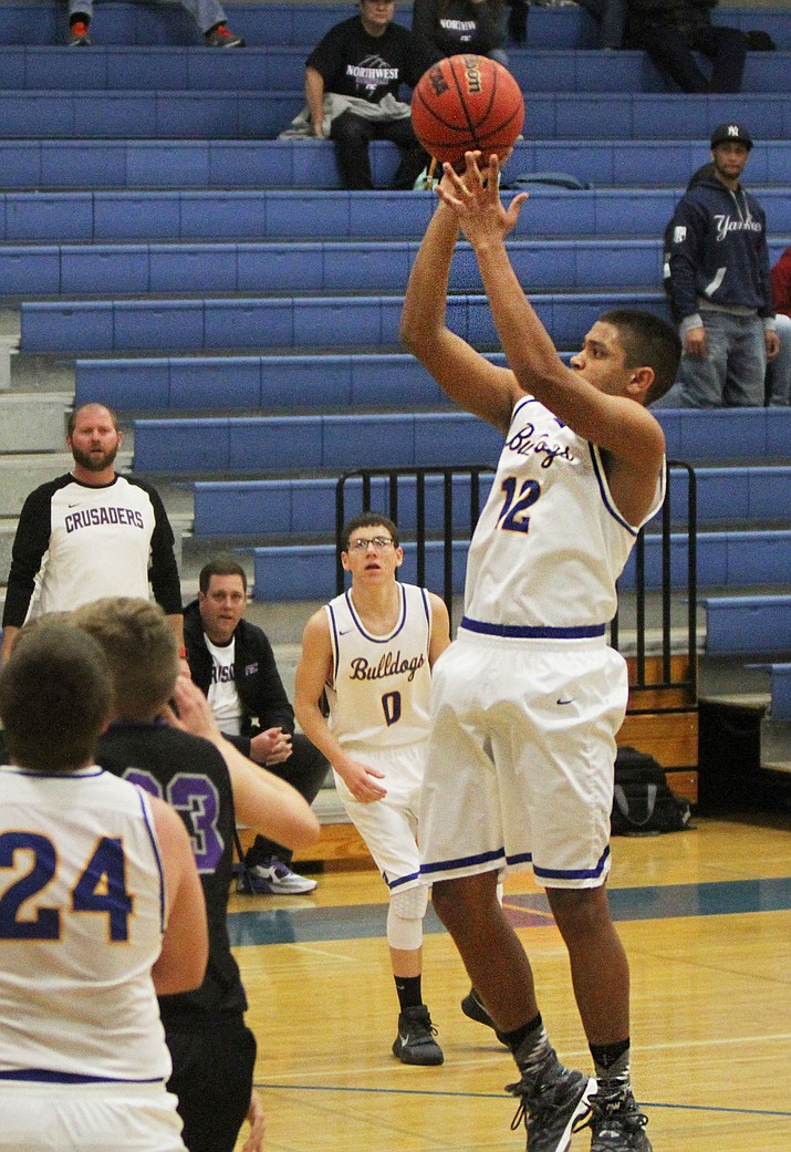Kingman's Tobias Bagby pull up for a short jumper during the Bulldogs' 63-56 loss to Northwest Christian Friday at KHS.