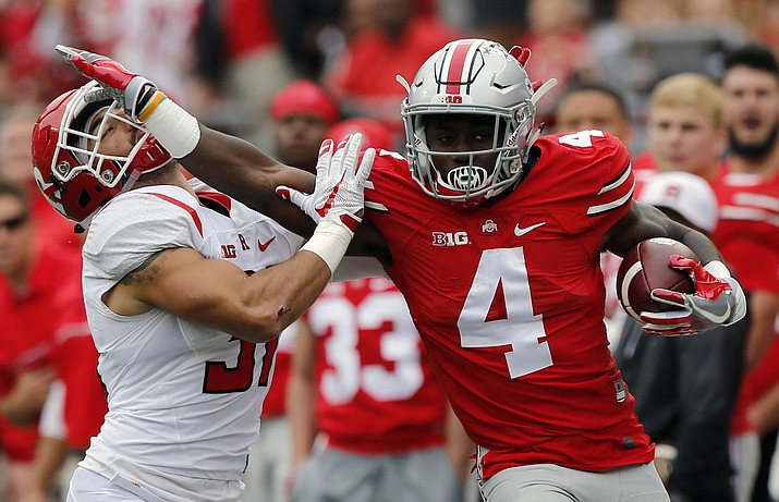 FILE - In this Oct. 1, 2016, file photo, Ohio State running back Curtis Samuel, right, stiff-arms Rutgers defensive back Anthony Cioffi during the first half of an NCAA college football game in Columbus, Ohio. Samuel is giving up his final year of eligibility to enter the NFL draft.
