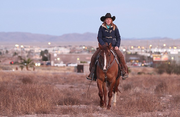 Sharla Wilson rides her mustang, Scarlet, with the shine of Kingman city lights behind her Friday evening.