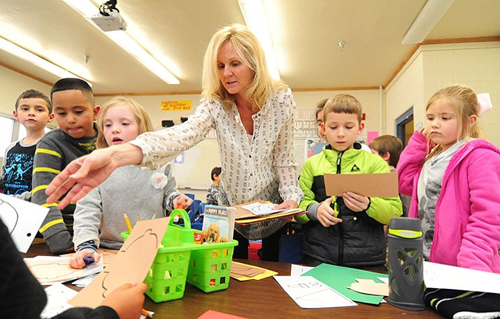 Coyote Springs Elementary School second-grade teacher Yvonne Berry hands out project materials during class Monday in Prescott Valley. Gov. Doug Ducey is expected on Friday to include raises for teachers in his budget.