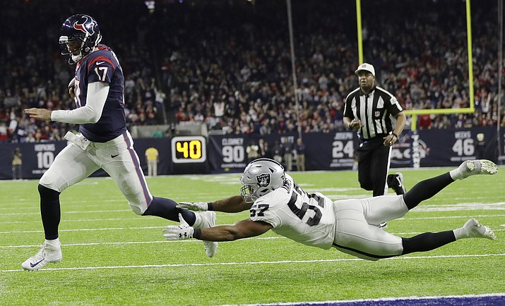Houston Texans quarterback Brock Osweiler scores on a two-yard run against Oakland Raiders' Cory James during their AFC Wild Card NFL football game Saturday, Jan. 7, in Houston. (Eric Gay/The AP)