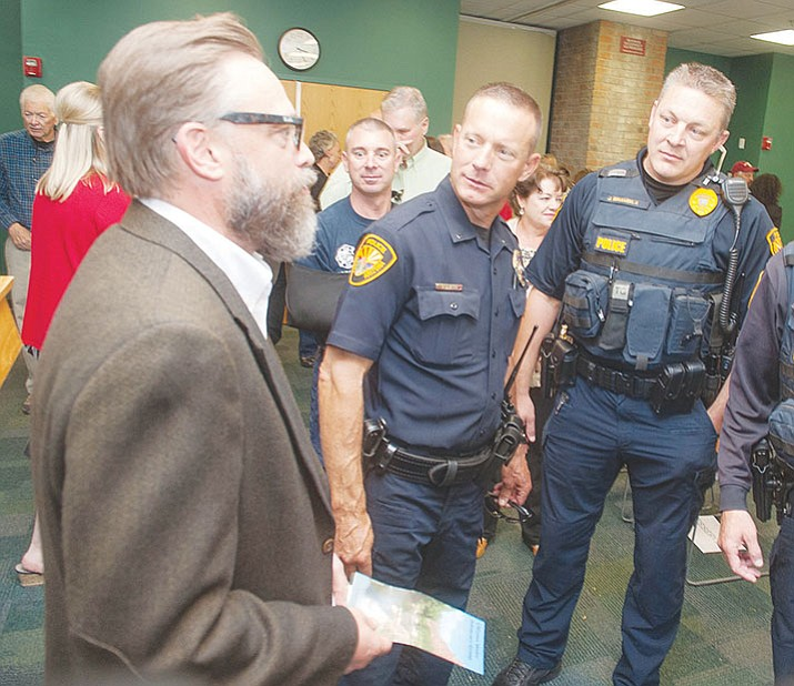 City Manager Michael Lamar, at his swearing-in in October, talks with Prescott Police lieutenants Rich Gill and Jon Brambila.