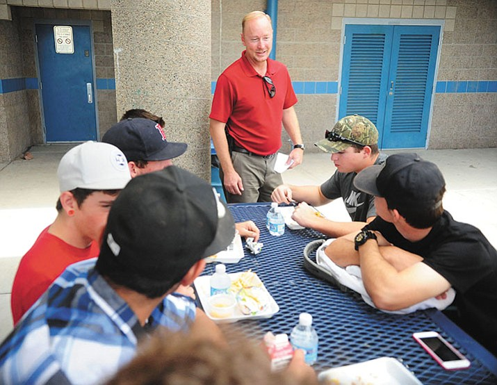 Chino Valley High School security officer Glenn Koester talks with a group of students about Friday night's football game during a lunch hour recently at the school.