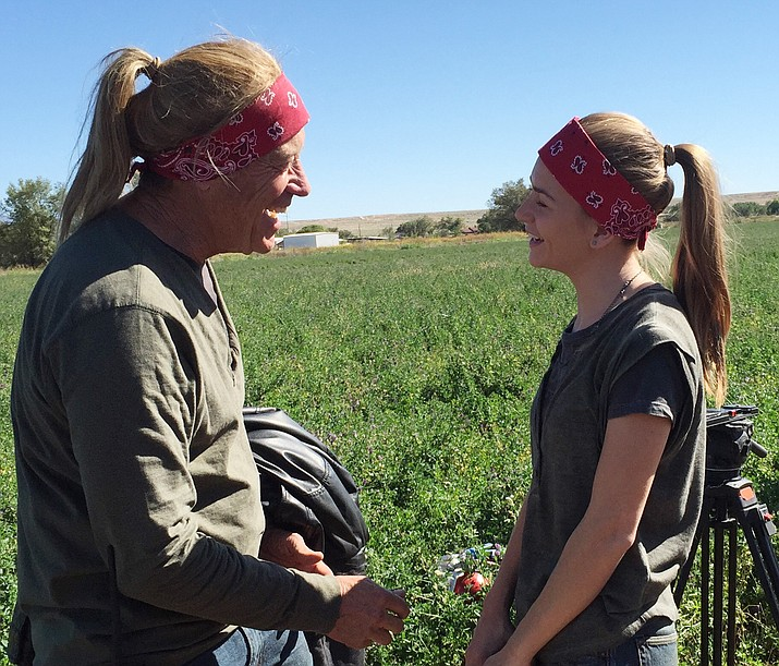 Stunt pilot and double Alan Hoover, left, in costume shares a moment on the set of the farmer's field near Albuquerque with Britt Robertson, who plays Tulsa in the film The Space Between Us.