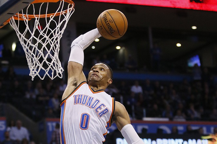 Oklahoma City Thunder guard Russell Westbrook (0) goes up for a dunk in front of New York Knicks forward Kristaps Porzingis (6) in the fourth quarter Feb. 15 in Oklahoma City. Oklahoma City won 116-105. (Sue Ogrocki/Associated Press)