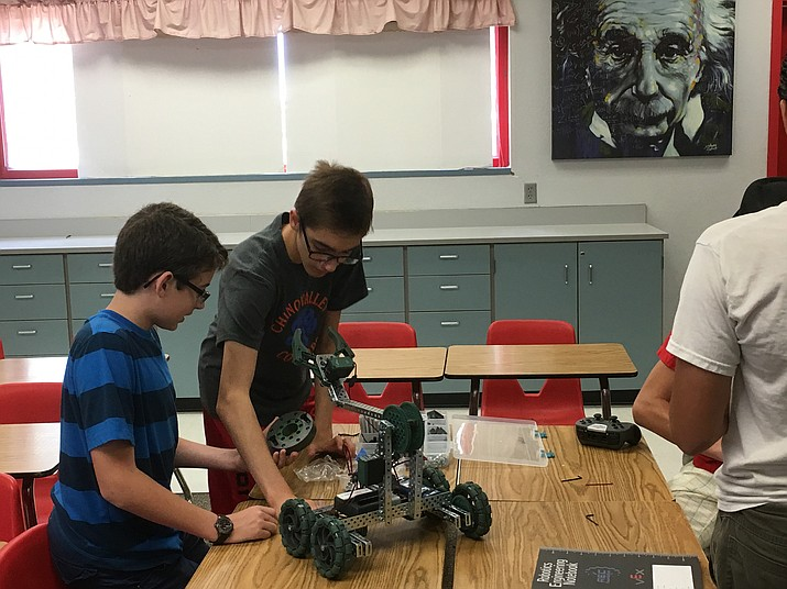 Jake Davis (center) works on the robot he is helping to build during a summer meeting of the robotics club on Monday, July 18 at Heritage Middle School.