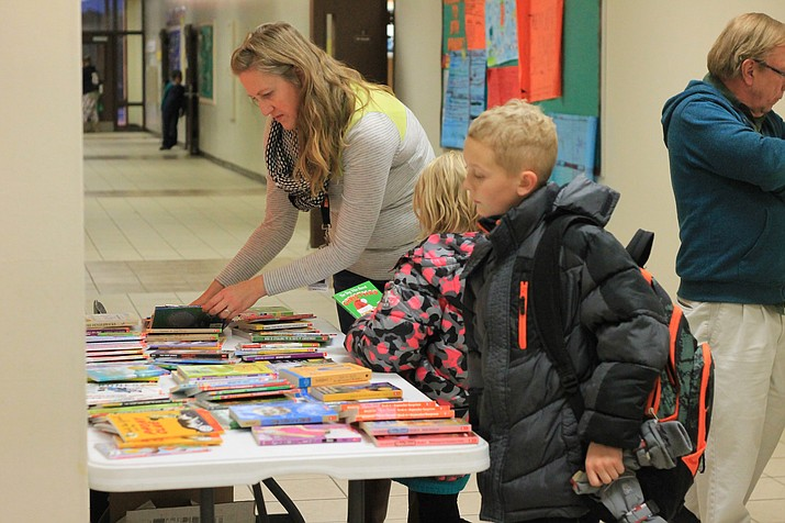 Christin Kopicky distrubutes books at the Family Literacy Night at WIlliams Elementary-Middle School Nov. 30.
