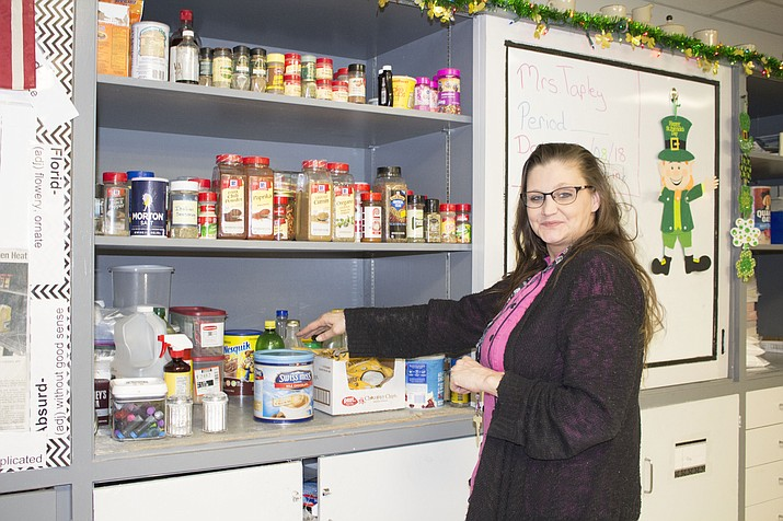Jamie Tapley, culinary teacher at Kingman Middle School, shows the cupboard of food in her classroom. She's starting an adult cooking class on the third Saturday of each month to raise money for stocking up on ingredients. (Photo by Hubble Ray Smith/Daily Miner)