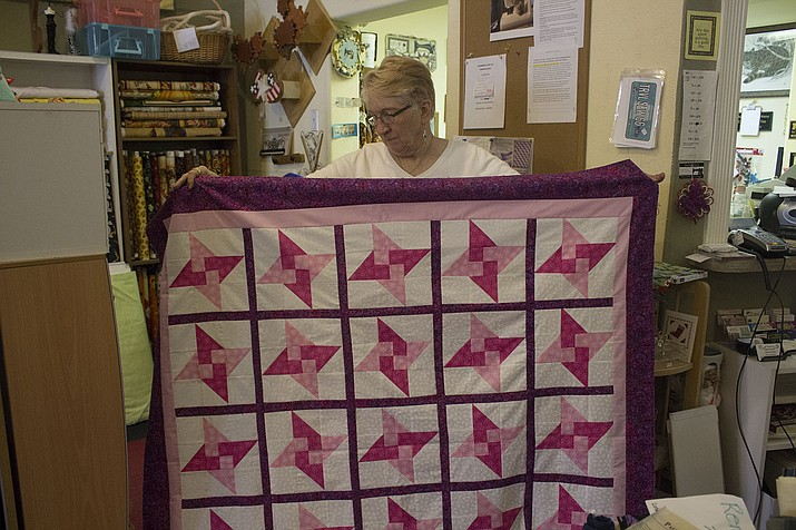 Connie Kettelhut of Connie's Quilters Hide-A-Way is holding one of the quilts that will be raffled away for the 'Quilt Pink for Life fundraiser' to raise money for breast cancer. (Photo by Vanessa Espinoza/Daily Miner)