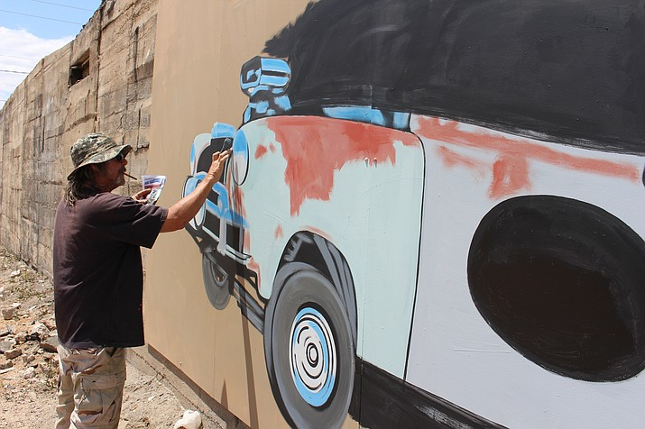 Dan, who did not want to give his last name, works on a mural for Rickety Cricket in downtown Kingman last year. Kingman Main Street plans more murals with its art alley project. (Daily Miner file photo)