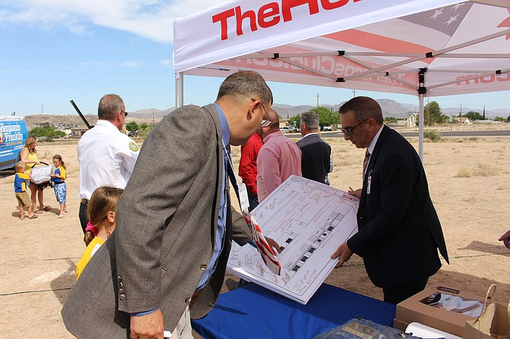 Larry Thornton, left, owner of Pitzer's One Hour Air Conditioning and Benjamin Franklin Plumbing, looks over an architectural drawing of his new building coming to Hualapai Mountain Road with marketing director Chris Rolando at the site Wednesday. (Photo by Hubble Ray Smith/Daily Miner)