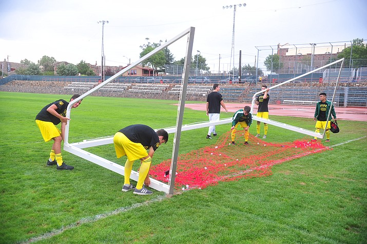 Yavapai College soccer players remove the goals from Ken Lindley Field in Prescott after learning that their match against Irvine Valley College of California was cancelled due to rain and lightning on Saturday, Aug. 25. (Les Stukenberg/Courier)