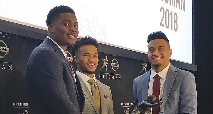 Heisman Trophy finalists, from left, Dwayne Haskins from Ohio State, Kyler Murray of Oklahoma, and Tua Tagovailoa from Alabama pose with the Heisman Trophy at the New York Stock Exchange, Friday, Dec. 7, 2018, in New York. (Ralph Russo/AP)