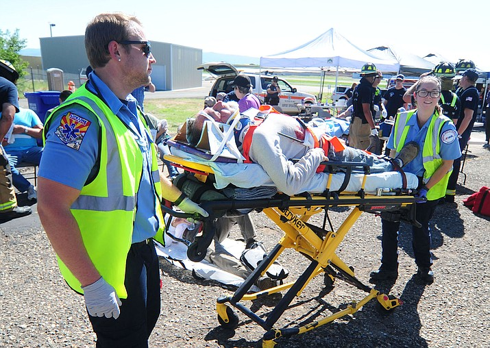 "Life Line Ambulance medics take a ""victim"" to a waiting helicopter as the Prescott Airport holds a mass casualty drill in August 2017. (Les Stukenberg/Courier file)"