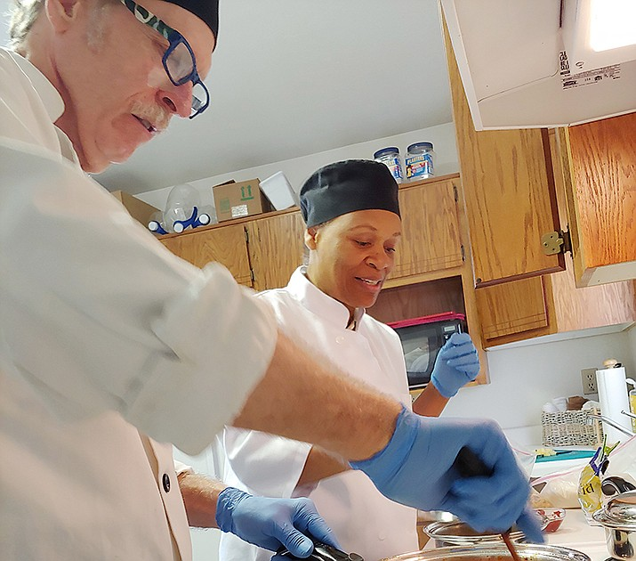 """Chefs Charles and Carmen Cole demonstrate how they cook a vegan Asian entrée, """"Sweet 'n Sour Tofu, Soy Curls, or Seitan,"""" at their home in Cordes Junction near Mayer. The Coles, who recently started their own business called Practical Healthy Living Chef Services, cook meals at their clients' residences in the Quad Cities, Anthem and north Phoenix. (Doug Cook/Courier)"""