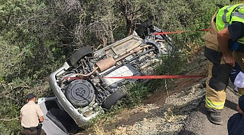 Woman rescued after car rolls down hill in Prescott photo