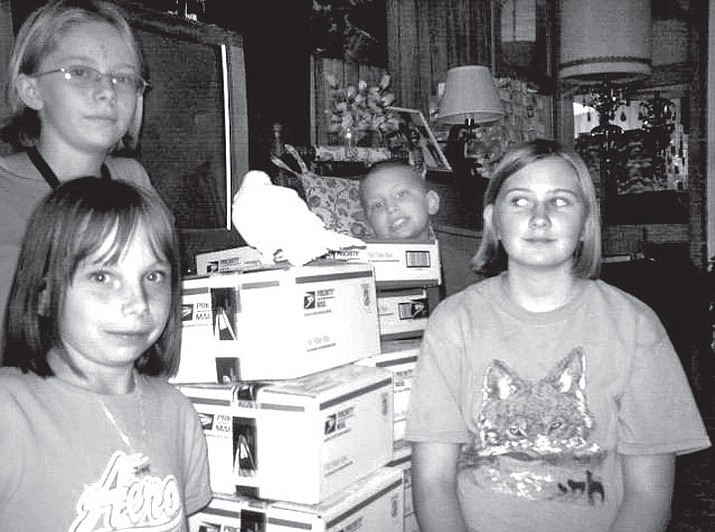 Courtesy Photo/Barbara Myers Lonesome Valley 4-H Wranglers (l-r) Evelyn Blasco, Emily Blasco, Nick Freibott and Amanda Myers finish packing care packages for troops overseas.