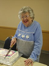 Betty, with a big birthday smile, cuts her cake.<br> Photo courtesy Pat Williamson