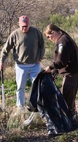 AFNM Park Ranger Nancy Stallard works with volunteer Mike Corder to clean the parking area at Badger Springs.<br> Big Bug News/Diana Baker