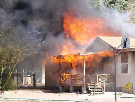 Fire completely destroyed this home on Topaz Road in Black Canyon City Saturday. A BCC captain rescued two firefighters who became disoriented in the home while fighting the fire.<br> BBNPhoto/Diana Baker