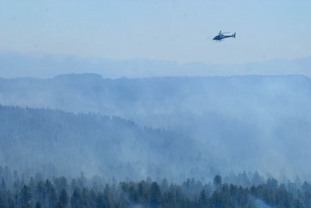 In an August 18 photo, a helicopter flies over the smoke from the Taylor fire near Sycamore Canyon southwest of Flagstaff. Arizona and the western third of New Mexico have seen a lackluster summer rainy season, leading to warmer temperatures and keeping wildfire danger high later in the year than normal.<br> AP Photo/ Arizona Daily Sun, Josh Biggs