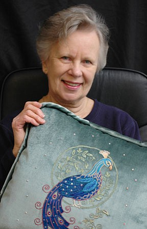 Spring Valley resident Joanne Fedden shows one of the elegant one-of-a-kind pillows she crafts using peacock designs and Swarsovski crystals.<br> BBNPhoto/Cheryl Hartz