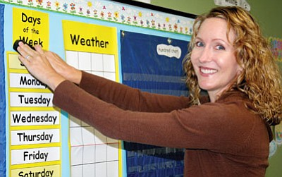 Katherine Williams finishes putting up a bulletin board in her classroom at Mayer Elementary School Monday morning. She anticipates 17 students will show up today in her combined first- and second-grade class.<br> Photo by Sue Tone
