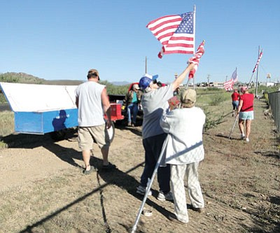 Chris Shackelford helps Lynn Hummel unfurl and raise a flag to help set up the Avenue of Flags.<br> Courtesy photo