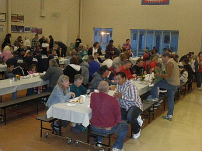 Hundreds of people filled the tables at the Community Thanksgiving Dinner, served by cheerful volunteers.<br> Photo courtesy Debbie Wells