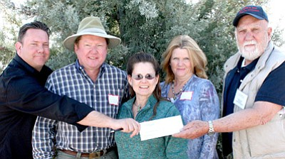 BBN Photo/Sue Tone<br>Brad Stafford, left, marketing director with Commspeed, passes a check for $250 to Ben Satran, president of the Arizona Highway 60 Chamber of Commerce, for the Festival, following the Chamber meeting on Feb. 8. Sam and Tina Knoy, second and third from left, with the Cordes Junction RV Park, donated $500, as did Cheri Brewer, second from right, with Black Canyon Dentistry.
