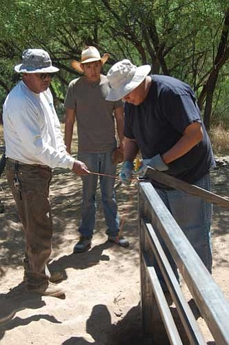 Photo courtesy Joanna Dodder<br /><br /><!-- 1upcrlf2 -->College students Peter Danner and Joey Tapaha help BLM Engineering Technician Amos Sloan build a fence to protect the Agua Fria River in the Agua Fria National Monument.