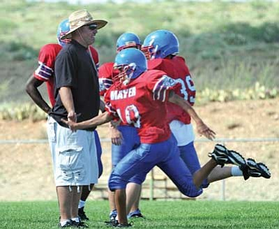 Photo courtesy Brett Soldwedel<br /><br /><!-- 1upcrlf2 -->Mayer High School Wildcats football coach Rick Lashley stands in as the finish line for Luke Vallo, No. 10, and Larry Hawkins, No. 39, during sprint drills in 2010 pre-season practice. Lashley said Mayer is changing some of its defense and offense schemes this season.