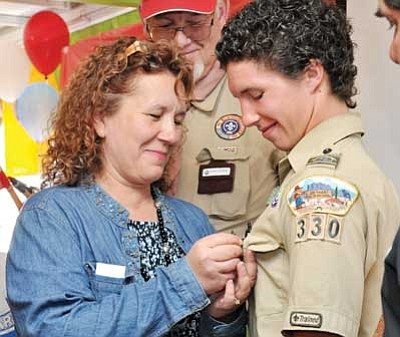 BBNPhoto/Heidi Dahms Foster<br /><br /><!-- 1upcrlf2 -->Angela Teskey Peterson pins the Eagle Scout badge on her son, John Alder, as his stepdad, Scout Committee Chairman Tom Peterson, center, looks on during John's Eagle Court of Honor Sunday.