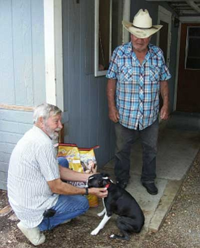 Courtesy Photo<br /><br /><!-- 1upcrlf2 -->Volunteer Paul Pollard greets Mayer resident Jerry Passmore's dog as he delivers dog food Wednesday. The food was provided through a Banfield Pet Hospital grant.