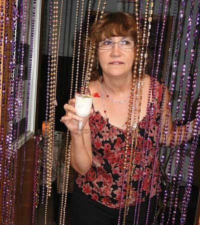 "Phyllis Hickey brings a drink from the ""speakeasy."" The annual event raised money for Meals on Wheels."