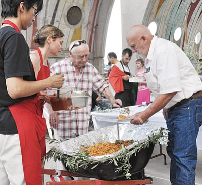 BBNphoto/Heidi Dahms Foster<br>Paolo Soleri has been a familiar sight through the years at Arcosanti's Italian Night, serving pasta from a wheelbarrow. Here, he serves Arizona Highway 69 Chamber President Ben Satran, right, as two helpers look on in 2011.