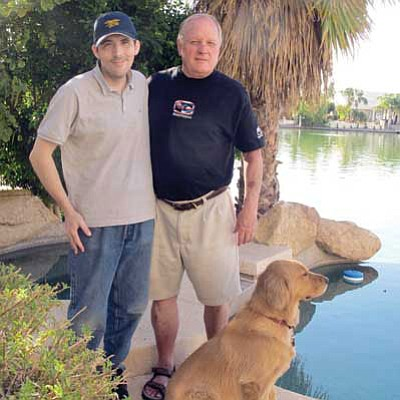 Courtesy photo<br> Mel McDonald stands outside his Valley of the Sun home with his stepson, Bennett, and Bennett's epilepsy special needs dog named Aggie.