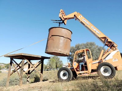 John Young operates a crane to place an old water tank on its new stand on Main Street, Humboldt, on Oct. 2. At one time in Humboldt's history, six tanks supplied the railroad hauling ore to the Val Verde (Humboldt) smelter. Kevin Leonard, owner of the tank, said holes are drilled in the tank so water cannot collect at the bottom.<br> Courtesy Photo