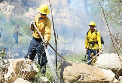 Les Stukenberg/PNI file. firefighters extinguish hotspots in a small wildland fire on April 20 near the trail system on the west side of the Laguardia Bridge in downtown Prescott. Officials are working to fix their pension system, which would require voter approval.