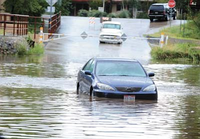 Les Stukenberg/ The Daily Courier, file<br /><br /><!-- 1upcrlf2 -->Someone drove their car into the confluence of Butte and Miller creeks at the Lincoln Avenue low-water crossing in Prescott and got stuck in the high water, this 2014 file photo shows. Monsoons can saturate soils and cause flash flooding. Experts warn people not to cross flowing water unless they can see the ground underneath it.