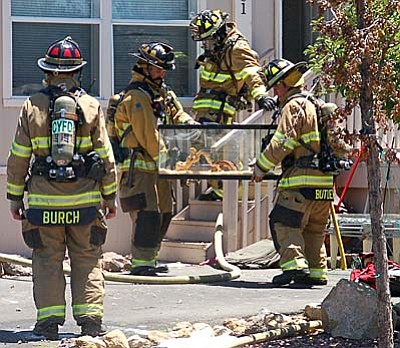 Les Bowen/The Daily Courier<br> Firefighters carry a snake with its cage from a house after a fire on Cattletrack Road in Prescott Valley on Monday afternoon, July 27. Yavapai Central Fire District personnel said there was extensive fire damage throughout the attic after the fire that started on the back porch.
