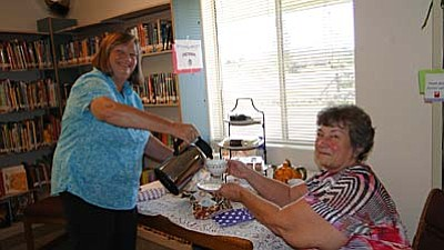 Pat Williamson/For BBN<br /><br /><!-- 1upcrlf2 -->Karon Trovillion pours tea for Cindy Simmons.