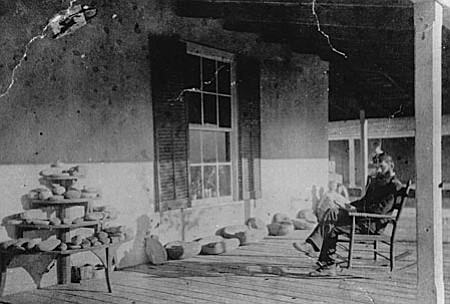 Post Surgeon Dr. Edgar Mearns on the porch of the Post surgeon's quarters at Fort Verde. Dr. Mearns served at Fort Verde from March 1884 to May 1888. The collection of metates on the porch is the result of Dr. Mearns' archaeological explorations of the prehistoric remains in the Verde Valley.